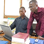 Joseph Oulai (left), Dan Bible translation team exegete, and Roger Tiemoko, translator on the Dan Bible project, in their office at SIL-RCI. Abidjan, Côte d'Ivoire. (project 74213)